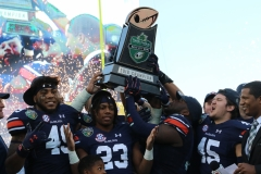 Auburn seniors Ryan Davis (No. 23 pictured), Darrell Williams (No. 49 pictured), Chase Cramer (No. 45 pictured) and Deshaun Davis (holding up trophy) celebrate the 2018 Music City Bowl  championship on the podium with their teammates.
